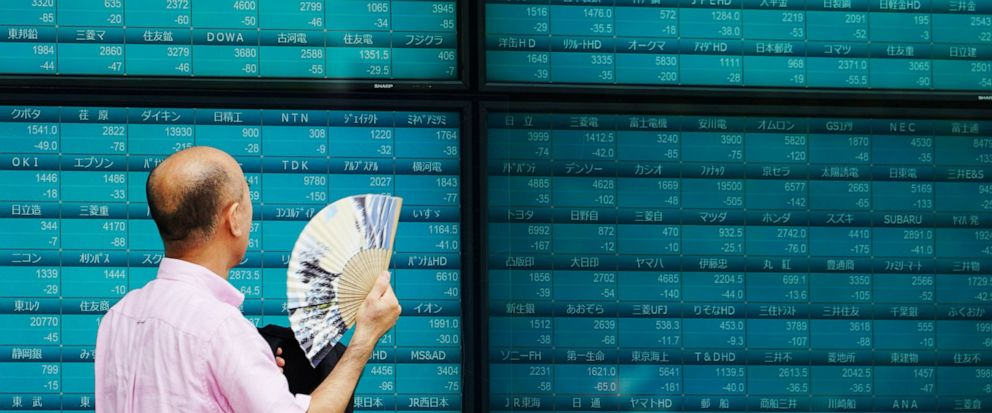 In this Thursday, Oct. 3, 2019, photo, a man looks at an electronic stock board showing Japans Nikkei 225 index at a securities firm in Tokyo. Asian shares were mixed Thursday, Oct. 10, following broad gains on Wall Street as investors pondered mixe