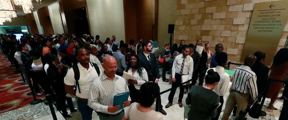In this Tuesday, June 4, 2019 photo, job applicants line up at the Seminole Hard Rock Hotel & Casino Hollywood during a job fair in Hollywood, Fla. On Friday, June 7, the U.S. government issues the May jobs report. (AP Photo/Wilfredo Lee)