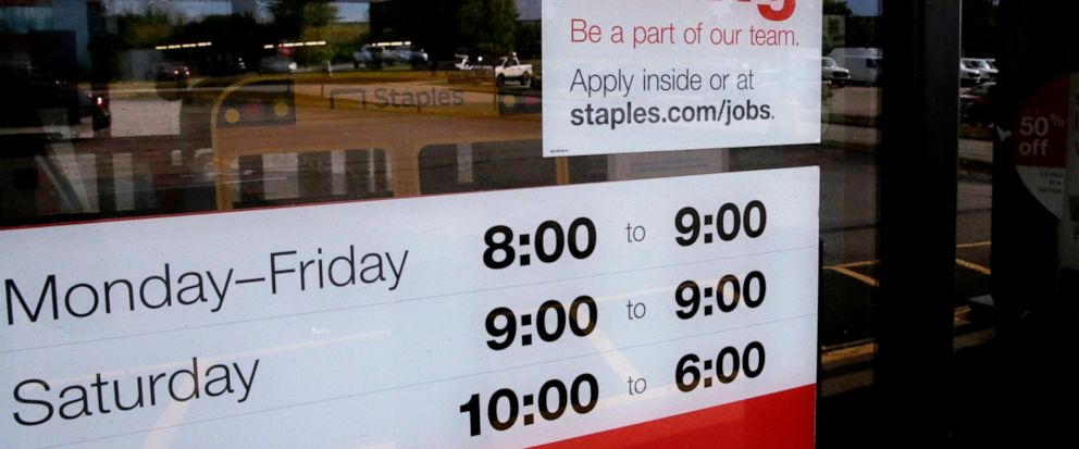 """FILE - In this Aug. 15, 2019, file photo a """"Now hiring"""" sign is displayed on the front door of a Staples store in Manchester, N.H. On Wednesday, Oct. 9, the Labor Department reports on job openings and labor turnover for August. (AP Photo/Charles Kru"""