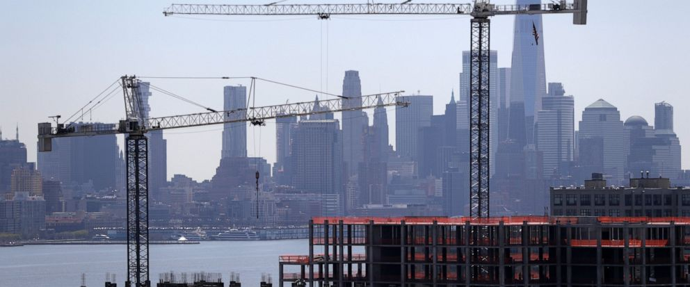 """FILE - In this April 23, 2019, file photo building cranes are seen at the construction site of a condominium complex with the Lower Manhattan skyline seen in the background in Weehawken, N.J. The Federal Reserve releases its latest """"Beige Book"""" surve"""