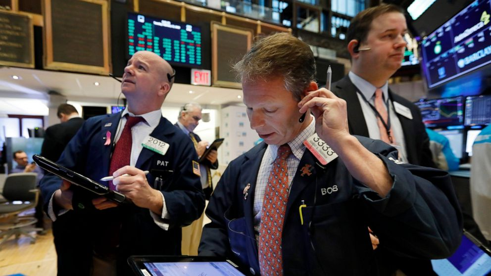 FILE- In this Feb. 12, 2019, file photo trader Robert Charmak, center, works on the floor of the New York Stock Exchange. The U.S. stock market opens at 9:30 a.m. EDT on Friday, April 12. (AP Photo/Richard Drew, File)