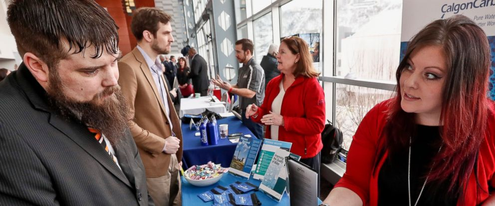 In this Thursday, March 7, 2019, photo visitors to the Pittsburgh veterans job fair meet with recruiters at Heinz Field in Pittsburgh. On Friday, March 8, the U.S. government issues the February jobs report, which will reveal the latest unemployment