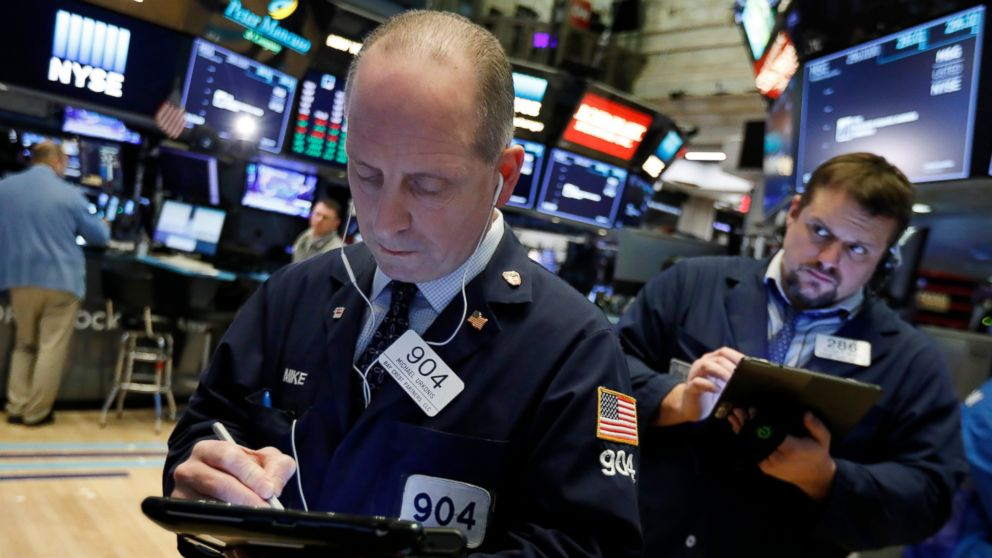 Trader Michael Urkonis, left, works on the floor of the New York Stock Exchange, Wednesday, March 13, 2019. U.S. stocks opened broadly higher on Wall Street Wednesday, powered by technology and health care companies, as the market pushes for its third straight day of gains. (AP Photo/Richard Drew)