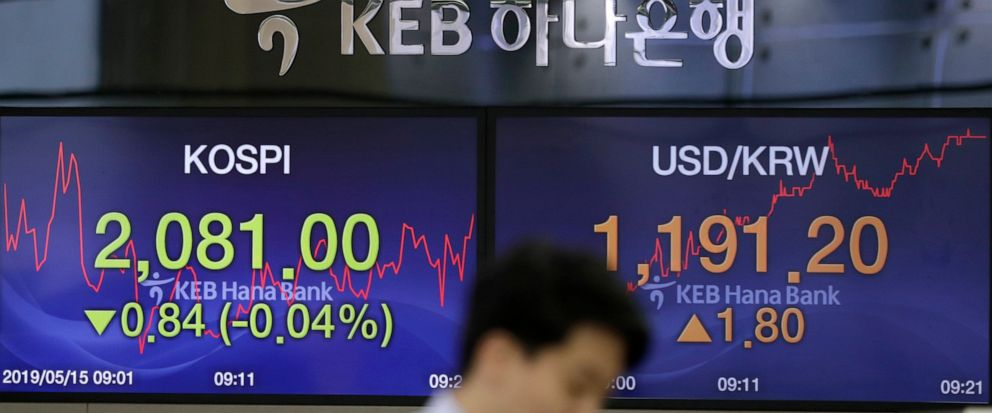 A currency trader watches the computer monitors near the screens showing the Korea Composite Stock Price Index (KOSPI), left, and the foreign exchange rate between U.S. dollar and South Korean won at the foreign exchange dealing room in Seoul, South