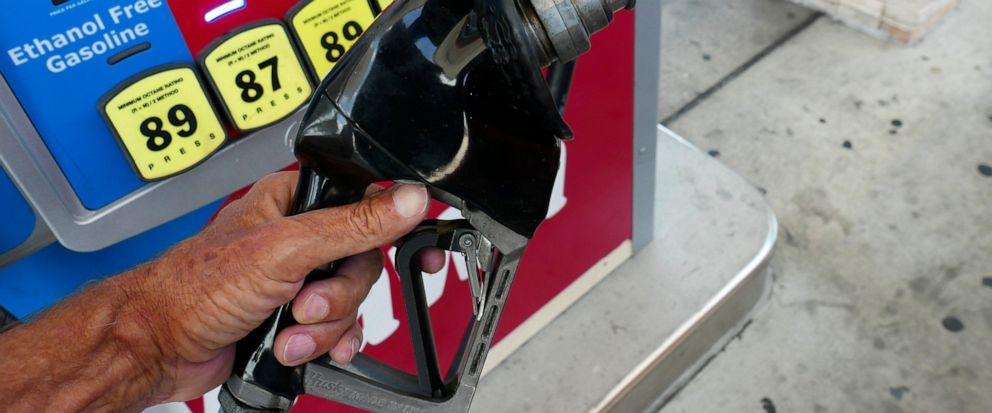 In this June 26, 2019 photo, a man adds fuel to his vehicle with the price of gas displayed at the pump at a gas station in Orlando, Fla. On Thursday, July 11, the Labor Department reports on U.S. consumer prices for June. (AP Photo/John Raoux)