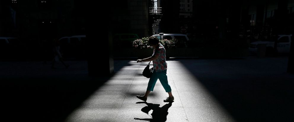 FILE - In this Sept 22, 2017, file photo a woman walks through a shaft of light on the Federal Plaza in Chicago. With 2019 more than one-third over, small business owners without employee retirement plans may want to consider starting one before more