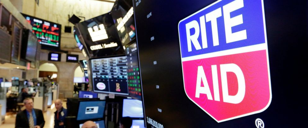 FILE- In this Aug. 9, 2018, file photo the logo for Rite Aid is displayed above a trading post on the floor of the New York Stock Exchange. Rite Aid will chop its share count by about 95% to make the remaining shares valuable enough to remain on the