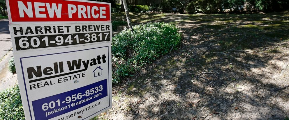 """In this June 13, 2019, photo a house on the market has a """"new price"""" sign fixed on the realtors sign in northeast Jackson, Miss. On Thursday, July 11, Freddie Mac reports on this week's average U.S. mortgage rates. (AP Photo/Rogelio V. Solis)"""