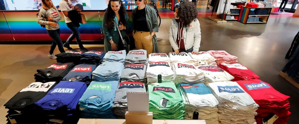 FILE- In this June 14, 2019, file photo a pair of shoppers, center, in the Levis store in New Yorks Times Square, survey a T-shirt display. On Tuesday, Aug. 13, the Labor Department reports on U.S. consumer prices for July. (AP Photo/Richard Drew, File)