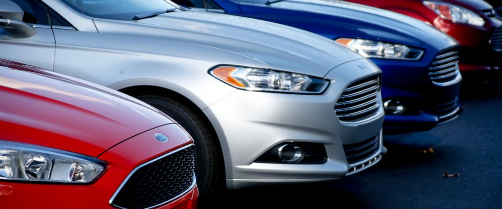 FILE- In this Nov. 19, 2015, photo, a row of new Ford Fusions are for sale on the lot at Butler County Ford in Butler, Pa. Ford is adding 270,000 vehicles to a recall in North America to fix a gearshift problem that could cause them roll away unexpec