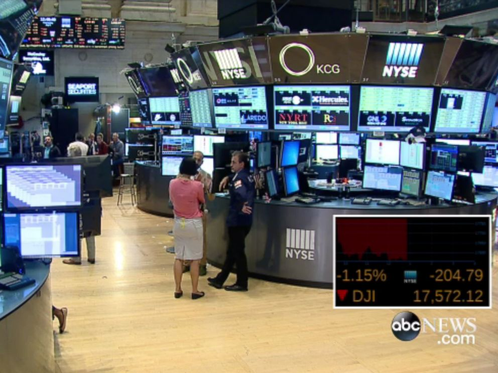 PHOTO: People stand around on the floor of the New York Stock Exchange after trading was halted on July 8, 2015.