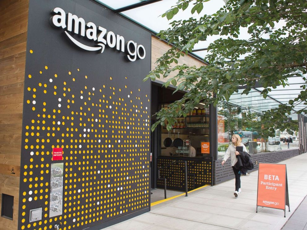 PHOTO: A woman walks past the Amazon Go grocery store at the Amazon corporate headquarters on June 16, 2017, in Seattle.