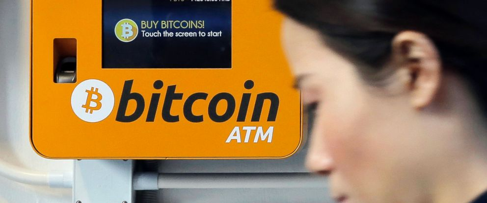 FILE - In this Dec. 21, 2017 file photo, a woman walks past the Bitcoin ATM in Hong Kong.
