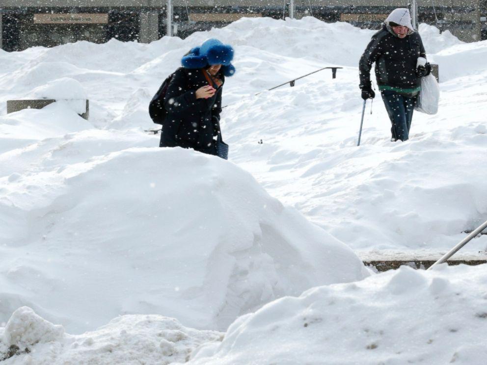 PHOTO: As snow flurries begin to fall again, pedestrians walk through Boston City Hall Plaza in Boston, Feb. 17, 2015.