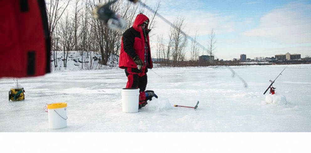 PHOTO: Michel Brunet braves the cold weather for a morning of ice fishing on the Saint Lawrence River along the shores of Montreal on Jan. 8, 2014.