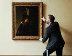 PHOTO: Curator of Pictures and Sculpture at Buckland Abbey, David Taylor adjusts the newly confirmed self-portrait by Rembrandt discovered at Devonshire Abbey, in Skipton, England, March 13, 2013.
