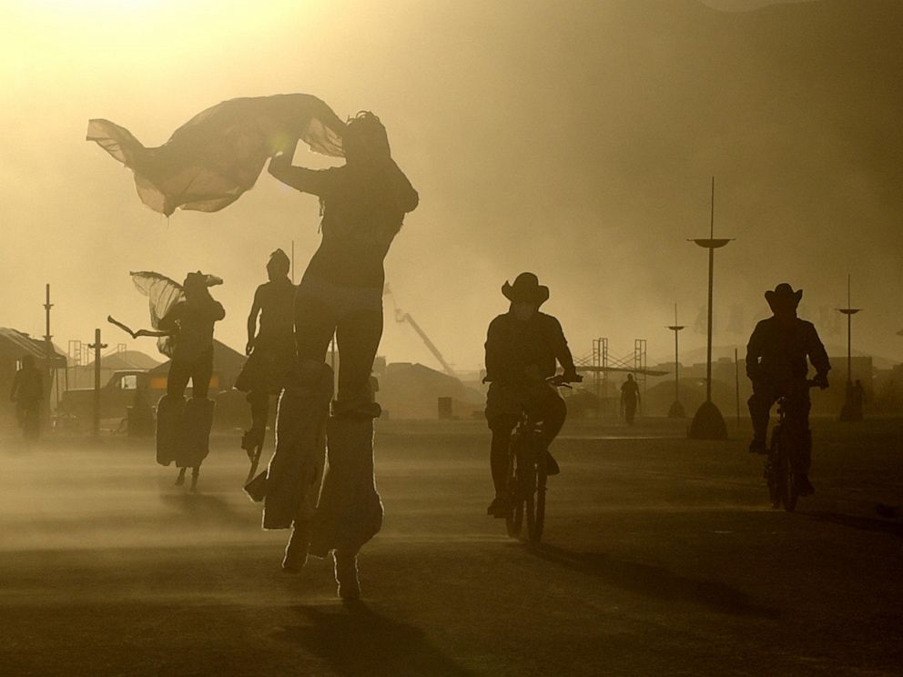 PHOTO: A windstorm whips sand at Burning Man as participants take evening bike rides and strolls on stilts in Black Rock Desert, Nev., Aug. 8, 2005.