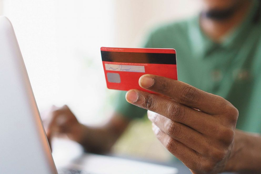 PHOTO: A man uses a credit card while shopping online.