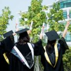A rear view of female graduates wearing graduation caps and gowns at campus is captured in this undated stock photo.