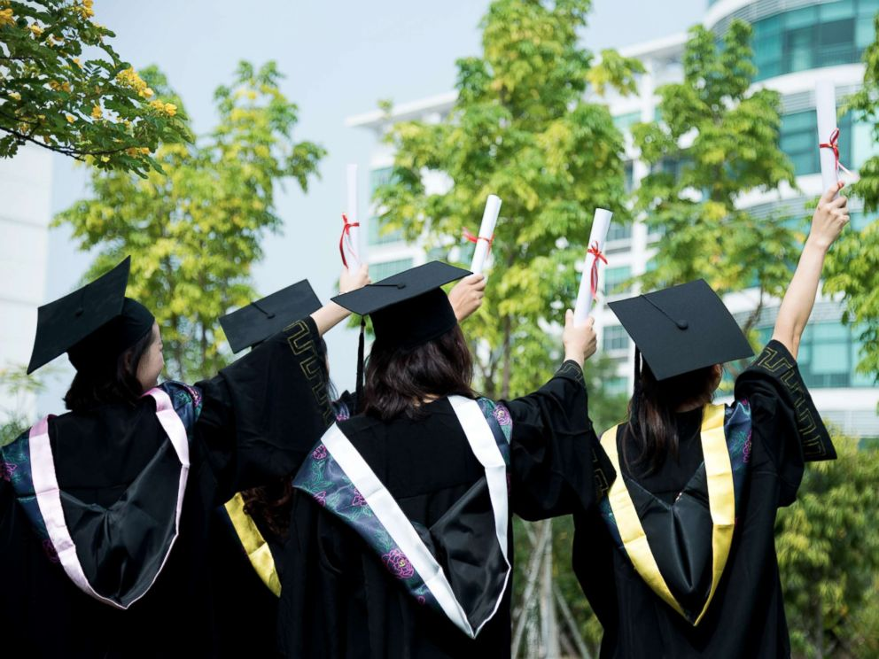 PHOTO: A rear view of female graduates wearing graduation caps and gowns at campus is captured in this undated stock photo.