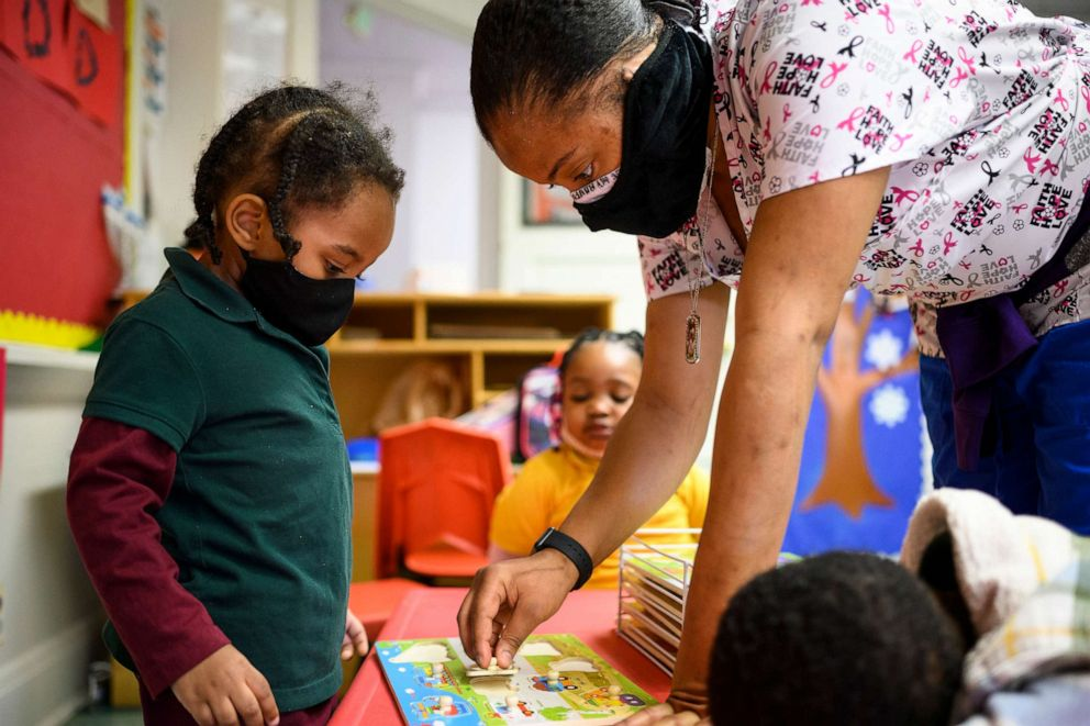PHOTO: Shanikia Johnson helps Magjor Jones clean up a puzzle at Little Flowers Early Childhood and Development Center in the Sandtown-Winchester neighborhood of Baltimore, Md. on Jan. 12, 2021.