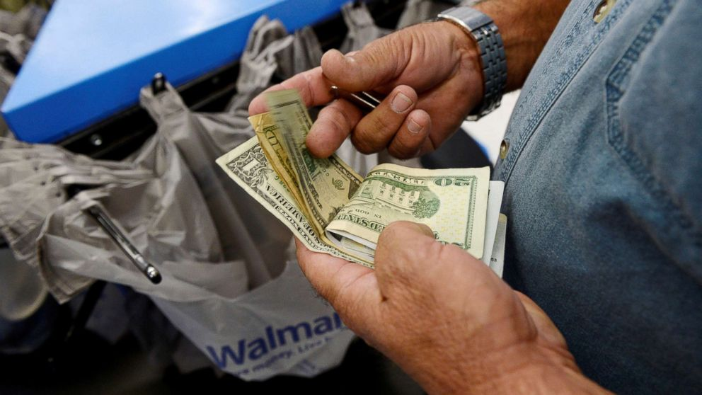 A customer counts his cash at the checkout lane of a Walmart store in the Porter Ranch section of Los Angeles, Nov. 26, 2013.
