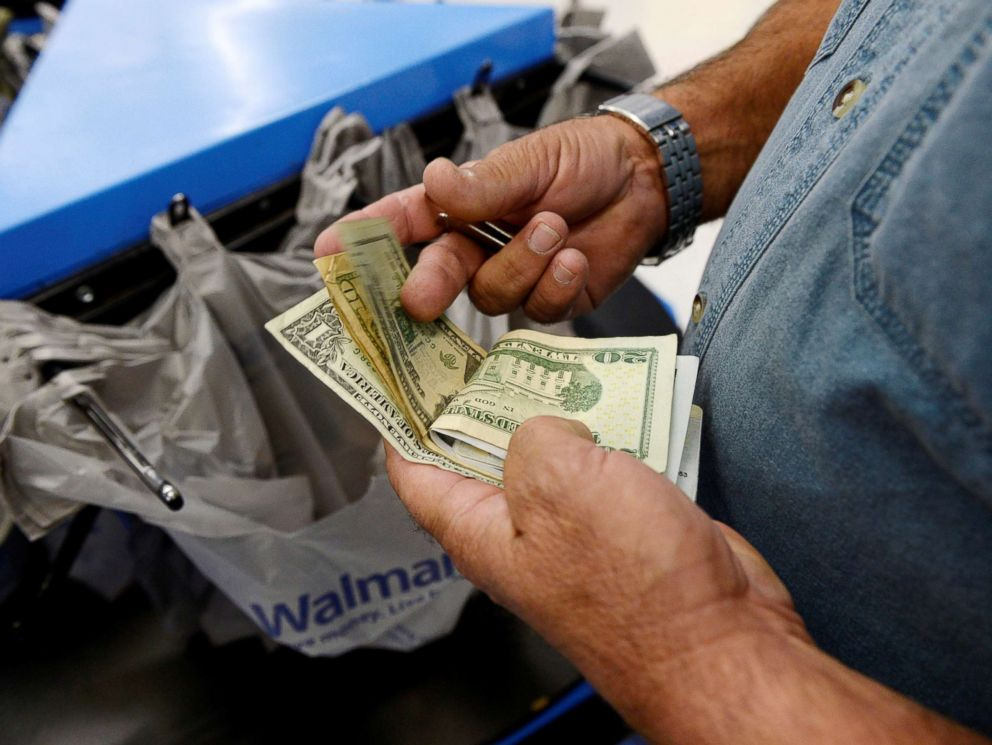 PHOTO: A customer counts his cash at the checkout lane of a Walmart store in the Porter Ranch section of Los Angeles, Nov. 26, 2013.