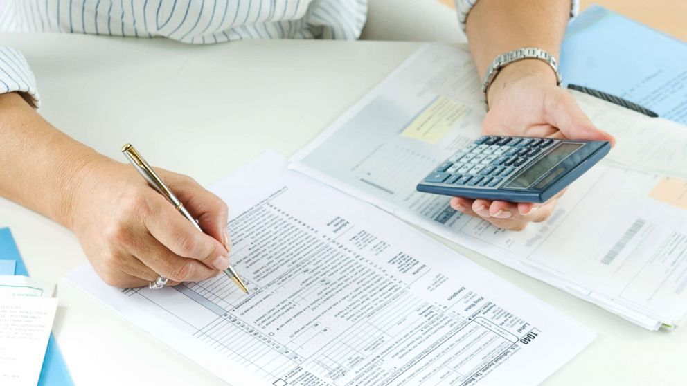 A woman calculates her taxes in this undated stock photo.