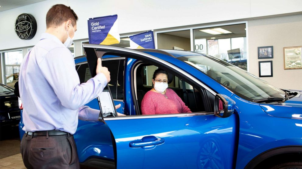 PHOTO: A potential Ford customer works with a sales associate at a local Ford dealership.
