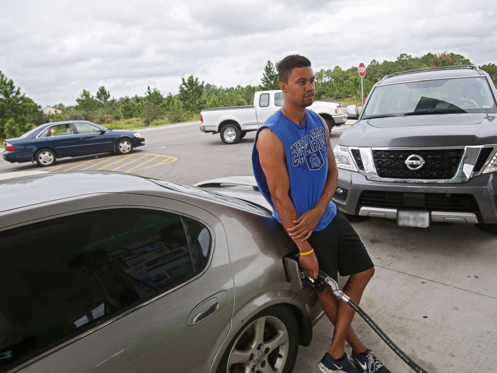 PHOTO: Andre Selby fills up his car while vehicles behind him line up for gasoline as people prepare for Hurricane Michael in Navarre, Fla., Oct. 9, 2018.