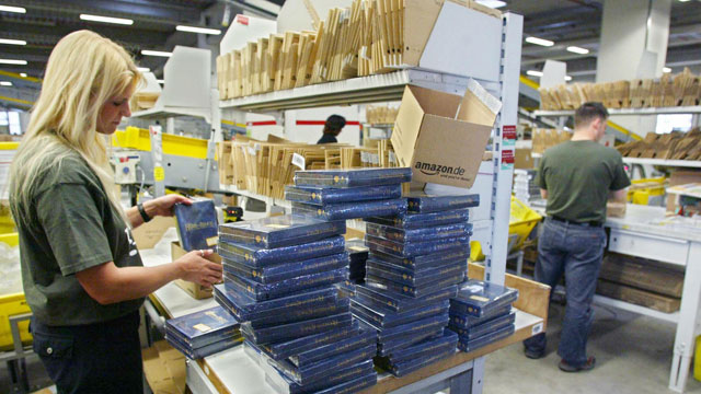 PHOTO: Employees of Amazon.de, the German branch of US online retailer Amazon.com, pack books into parcels ready to be sent to the clients, December 4, 2004 in Germanys Amazon distribution central in the western town of Bad Hersfeld.