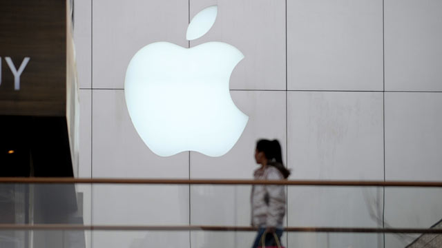 "PHOTO: A woman walks past an Apple store in Beijing on April 2, 2013. Apple chief executive Tim Cook has apologised to Chinese consumers after the US technology giant was subjected to a barrage of criticism in state-run media over alleged ""arrogance"" and"