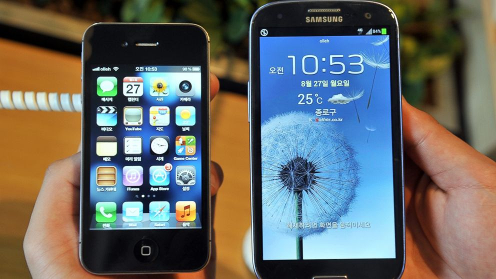 An employee shows an Apple's iPhone 4s (L) and a Samsung's Galaxy S3 (R) at a mobile phone shop in Seoul on August 27, 2012.