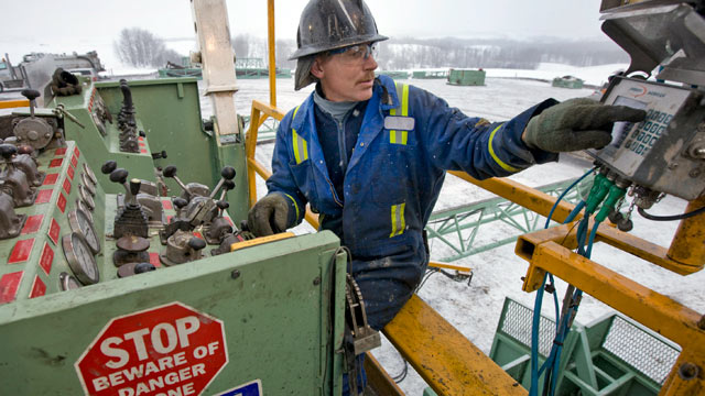 PHOTO: Driller Ian Van Egmond operates the controls for a spinning drill at an Encana Corp. natural gas well site near Alix, Alberta, Canada, Dec. 19, 2009.