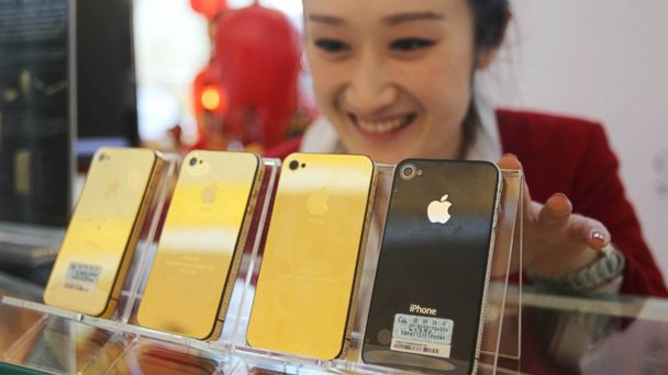 A shopkeeper shows golden accessories of Iphone at a shopping mall on March 25, 2011 in Qingdao, China.
