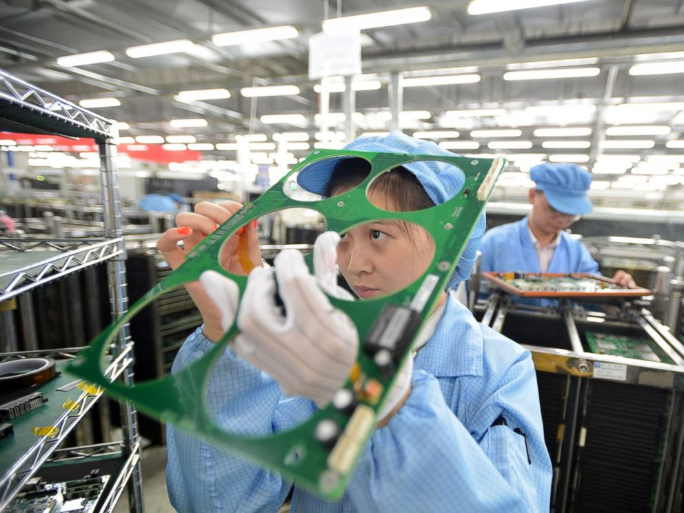 PHOTO: Employees work on the production line of a telecom equipment manufacturer on July 27, 2015 in Wuhan, China.