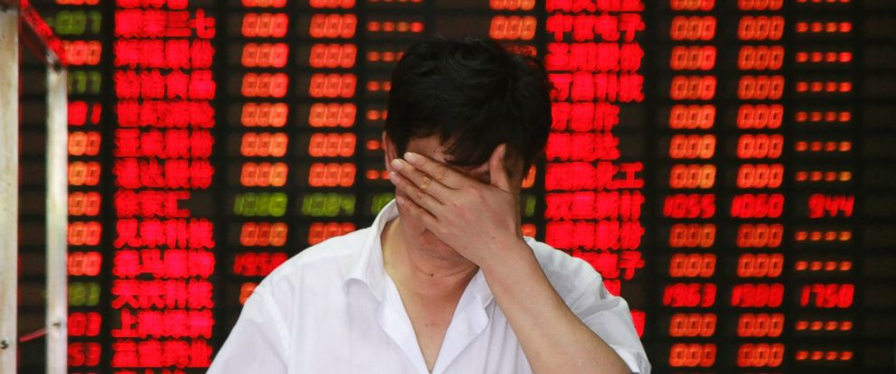 PHOTO: An investor covers his face while he walks out from a brokerage firm on July 8, 2015 in Shanghai, China.