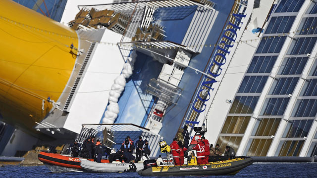 PHOTO: Rescue workers stand in small boats near the stricken cruise liner Costa Concordia lying aground in front of Giglio island, Jan. 26, 2012.