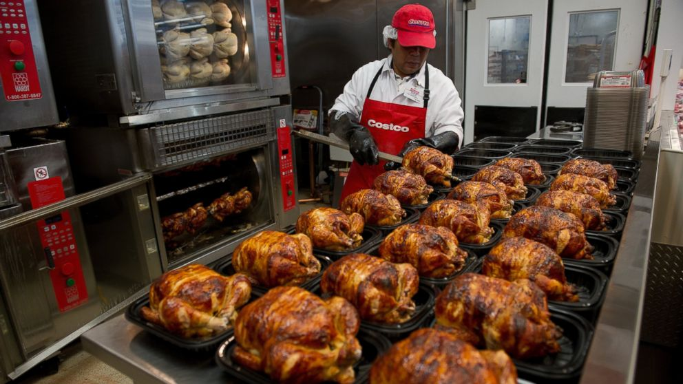 A service deli worker places cooked rotisserie chickens in containers at a Costco store in San Francisco, Calif. on Dec. 6, 2011.
