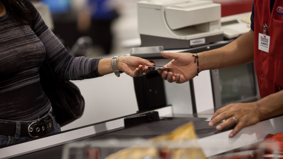 A customer hands the cashier her membership card to make purchases at the Costco outside of Mexico City on May 21, 2012.