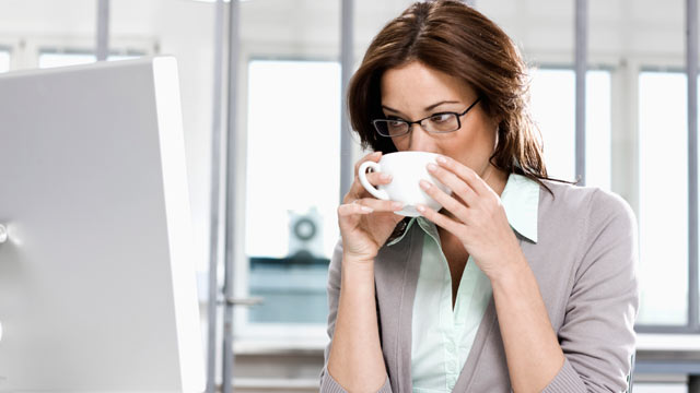 PHOTO: Seen here is a portrait of businesswoman sitting in front of computer drinking coffee.