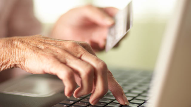 PHOTO: Close-up of Senior womans hands using laptop and holding a credit card.