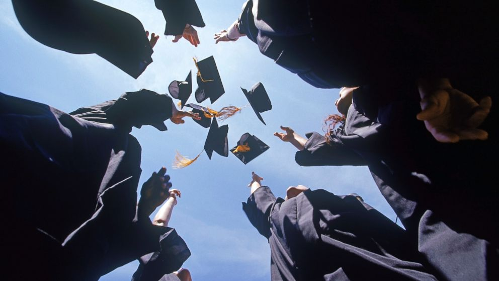 Graduates throw their caps in the air in an undated stock photo.