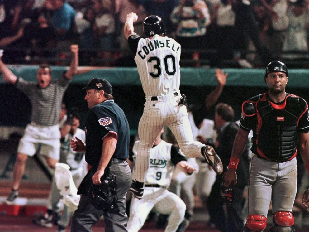 PHOTO: Florida Marlins player Craig Counsell jumps in the air after crossing the plate with the winning run as Cleveland Indians catcher Sandy Alomar walks off the field in game seven of the World Series, Oct. 26 1997, at Pro Player Stadium in Miami.