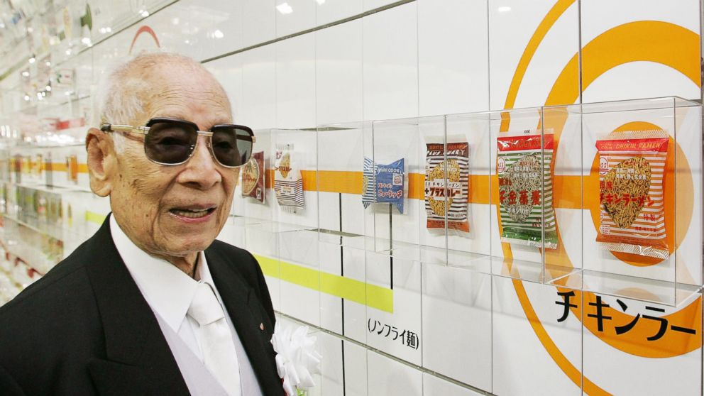 Momofuku Ando, the founder of Japan's Nissin Food Products Co., poses next to a package of company's historic first bag of chicken ramen which was introduced in 1958  at the refurbished Instant Ramen Museum in Osaka, Japan on Nov. 25, 2004.