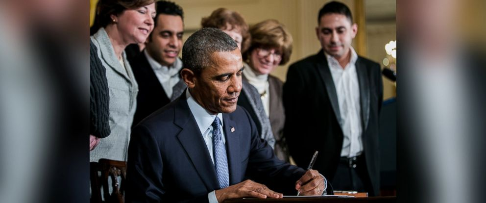 PHOTO: President Barack Obama signs a presidential memorandum on overtime protections while surrounded by salaried employees, business leaders and supporters at an event in the East Room of the White House in Washington, D.C. on March 13, 2014.