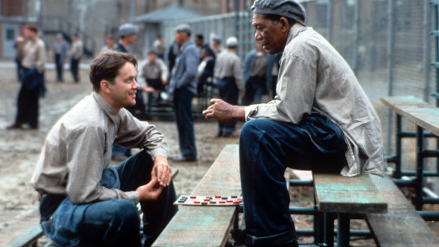 PHOTO: Tim Robbins and Morgan Freeman sitting outside on the benches playing checkers and talking in a scene from the film 'The Shawshank Redemption'.