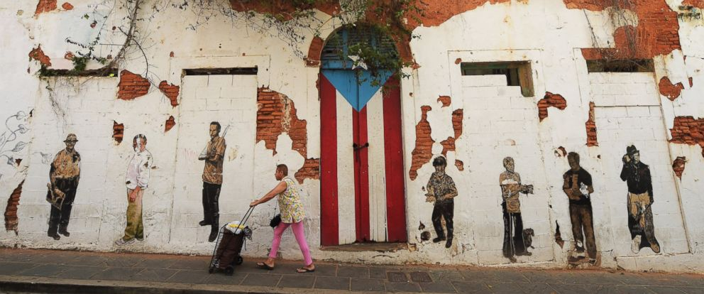 PHOTO: A woman walks by a rundown building on Saturday July 04, 2015 in Old San Juan, Puerto Rico.