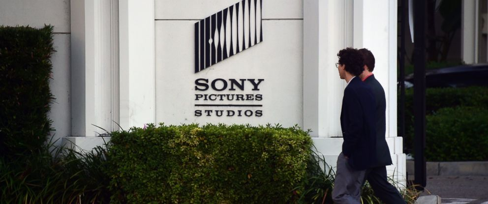Sony pictures plans town hall as hackers promise christmas gift to photo pedestrians walk past an exterior wall to sony pictures studios in los angeles negle Image collections