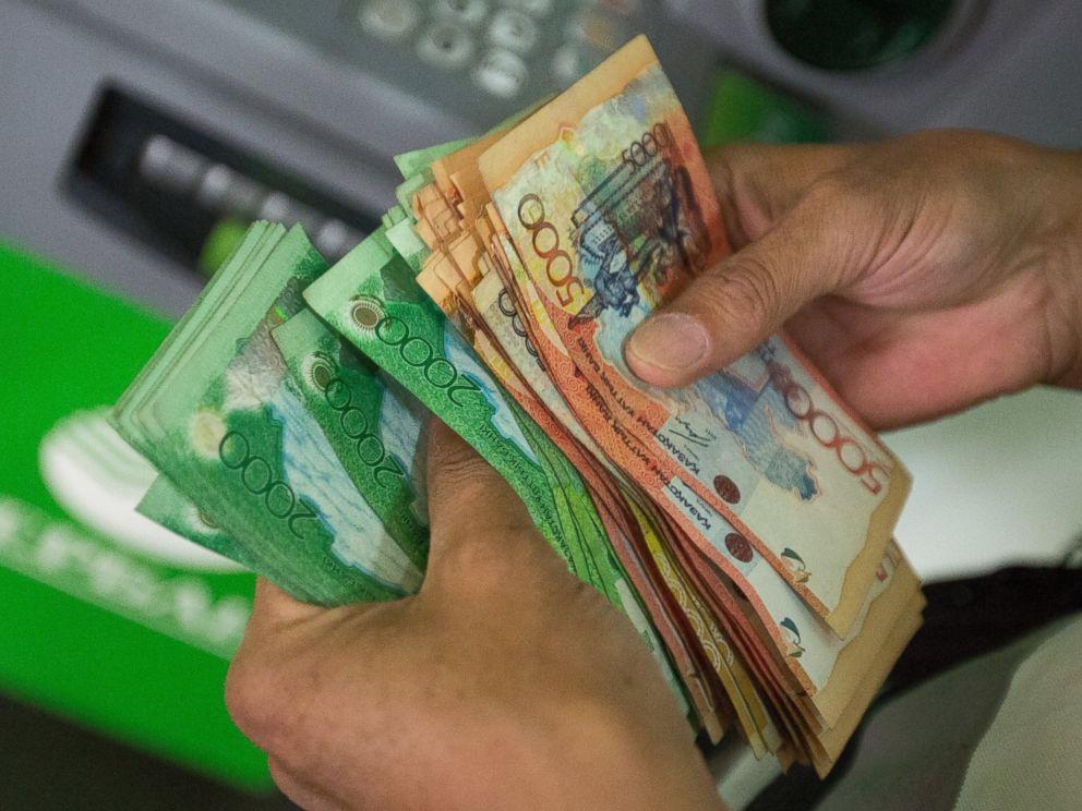 PHOTO: A customer counts tenge currency banknotes inside a bank in Almaty, Kazakhstan, June 23, 2015.